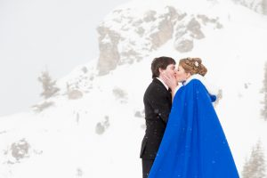 A bride kissing her groom on a snowy mountain top