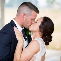 A birde and groom kissing at the altar, beautiful makeup by bri stein