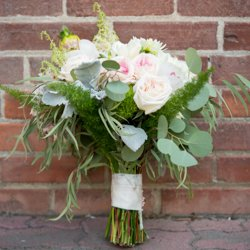 Wedding florals leaning against a brick wall