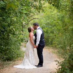 A couple standing in a treed pathway
