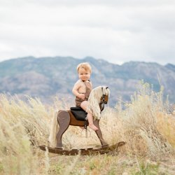 A baby boy sitting on an antique rocking horse