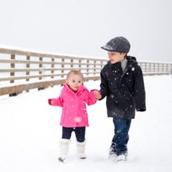 A brother and sister holding hands in the snow, walking up the wharf