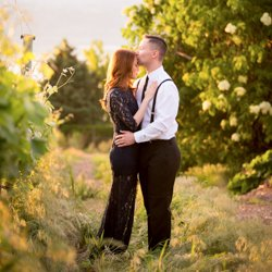 A man kissing a woman on the forehead in a vineyard