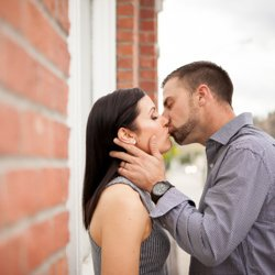 A couple kissing against a brick building downtown