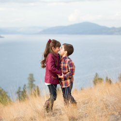 A brother and sister eskimo kissing in front of an Okanagan Lake view