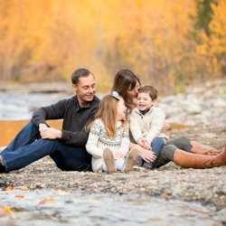 A family sitting be a creek, laughing in the Fall