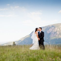 A bride and groom kissing on a grassy hill on their wedding day