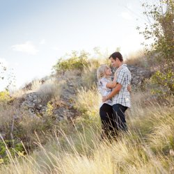 A couple hugging in the long grass as Kalamalka Lake Park