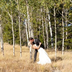 A groom dipping his bride in the aspen trees