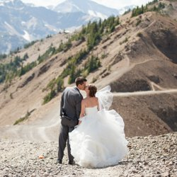 A birde and groom kissing on a mountain topm with the bride's veil blowing in the wind