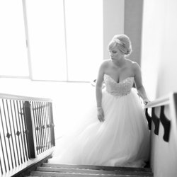 A bride standing on a staircase at the Prestige Hotel