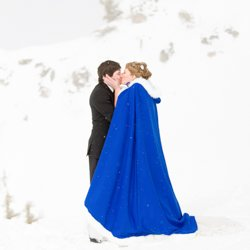 A birde and groom kissing in the snow on a mountain top