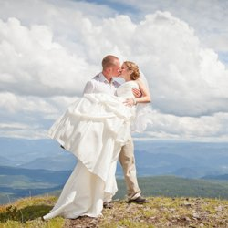 A grrom picking up his bride on a mountaintop on their wedding day