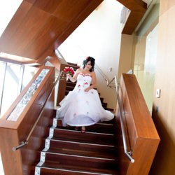 A birde walking down a staircase in her wedding dress