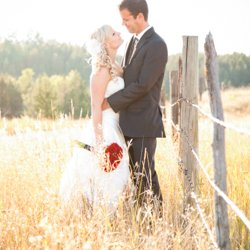 A bride and groom standing by a wodden, barbed wire fence in the sunlight