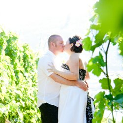 A couple kissing in a vineyard with the sun shining