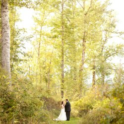 A couple standing together in the trees on their wedding day
