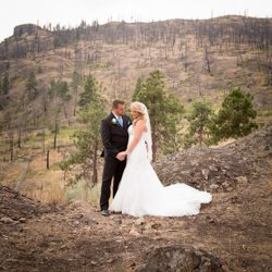 A couple holding hands on a mountain with burnt trees from a forest fire in the background