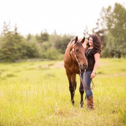 A girl with her horse standing in an open field