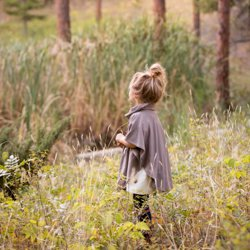 A little girl standing by a pond