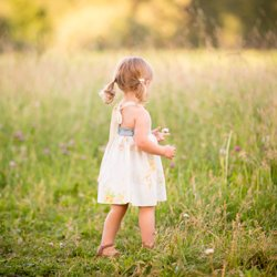 A little girl in pig-tails and a sundress picking a wild flower