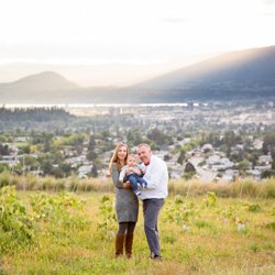 A family snuggling in front of a beautiful Okanagan Valley view