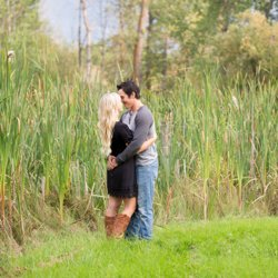 A couple hugging in the grass beside the cattails