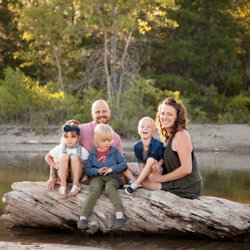 A family sitting on a twisted log in the water