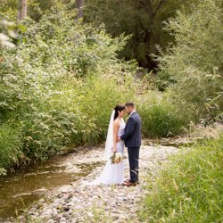 A bride and groom standing together by the creek