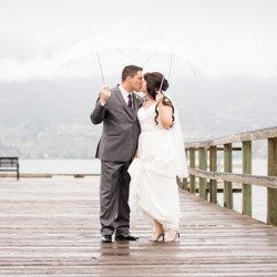 A couple kissing in the rain under two umbrellas