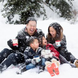 A family laughing in the snow together drinking hot chocolate