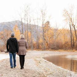 A couple walking hand-in-hand along the beach in fall