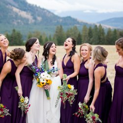 A bridal party laughing in an open field