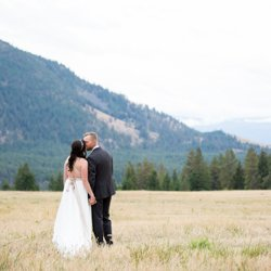 A couple kissing in an open wheat field at Shylyn Ranch