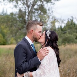 A bride and groom kissing in the rain