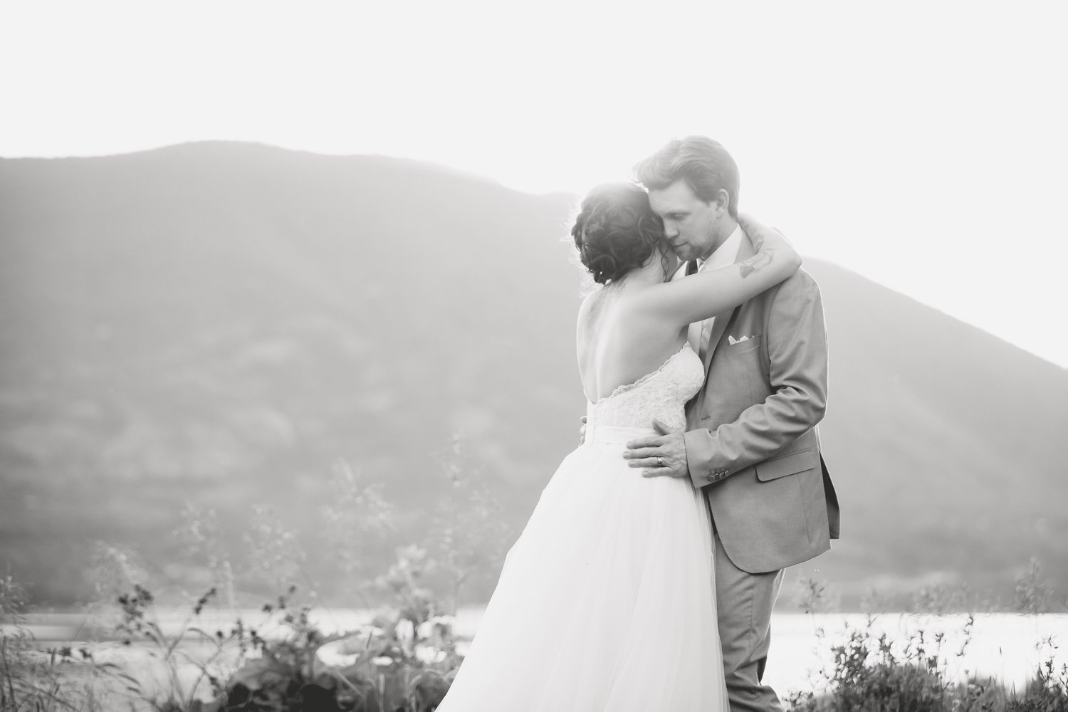 A couple hugging in front of a lakeview on their wedding day