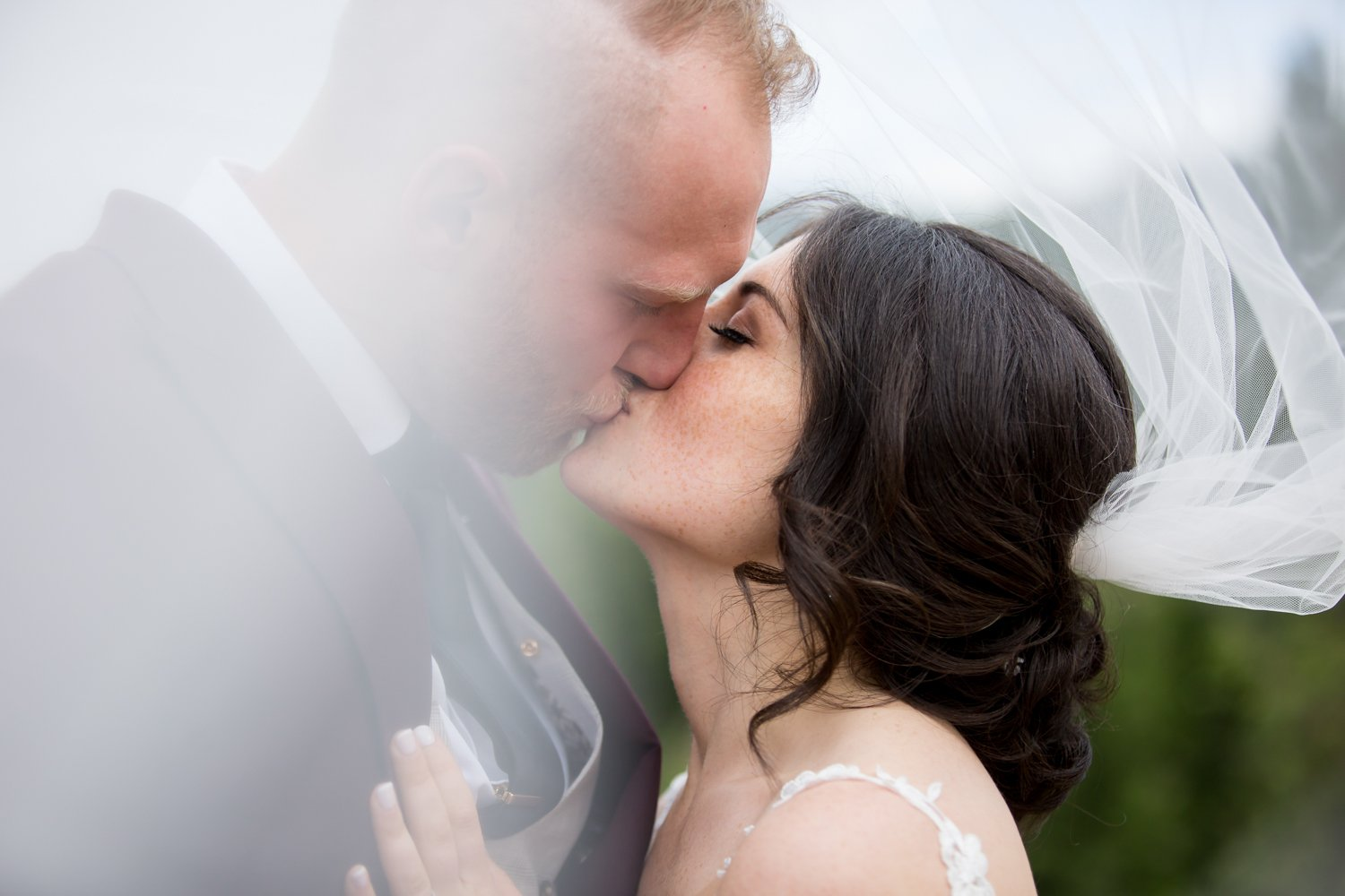 Bride and groom kissing under a veil