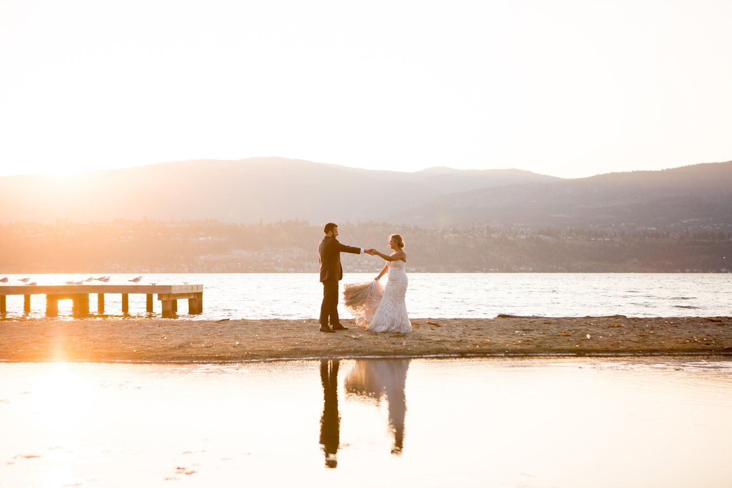A bride and groom dancing in the sunlight at golden hour