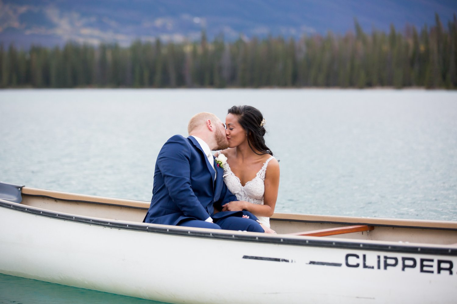 A couple kissing in a canoe on their wedding day