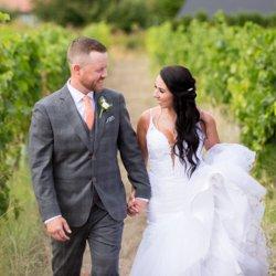 Couple walking through vineyard on wedding day