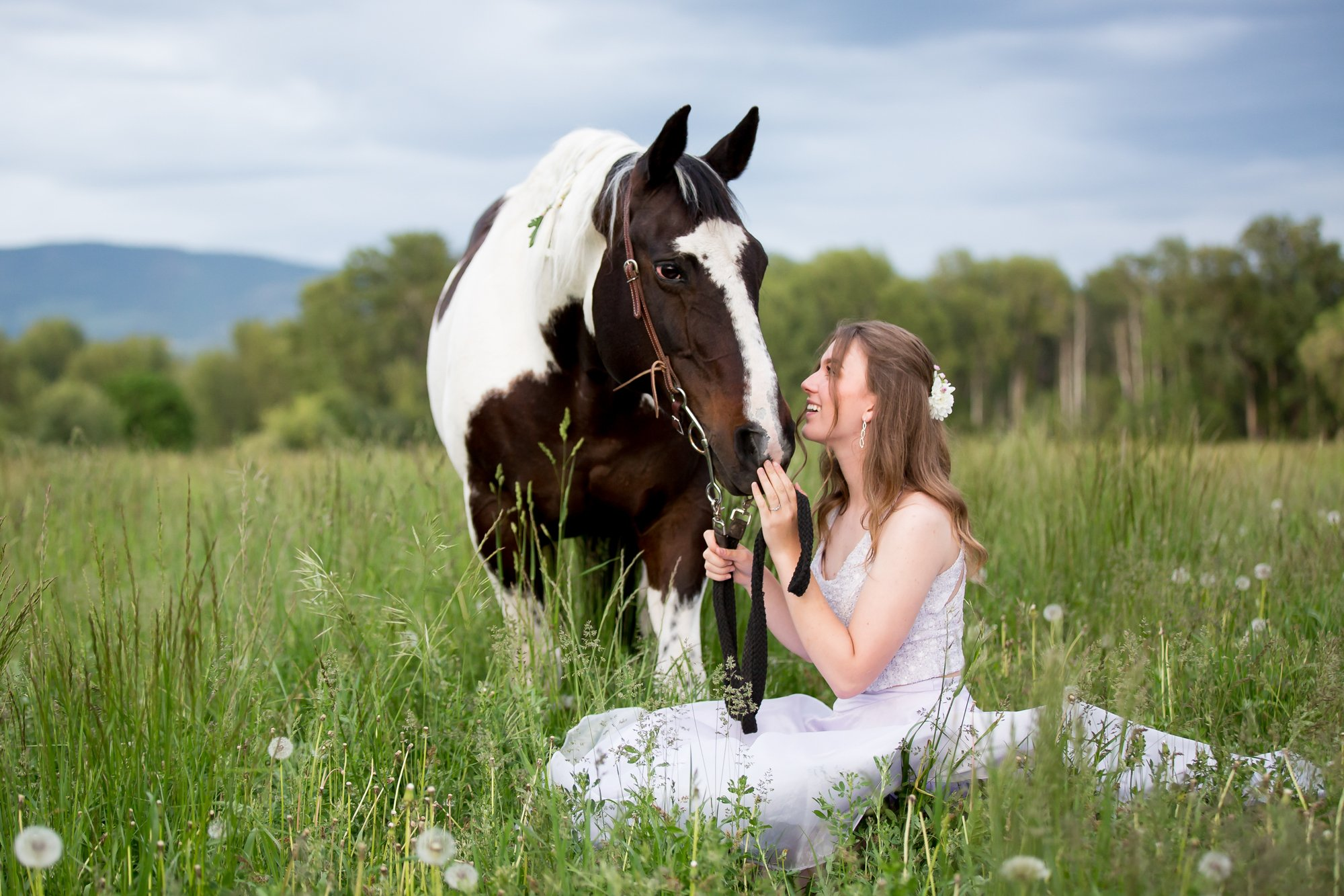 A gorl sitting on the grass looking up at her horse