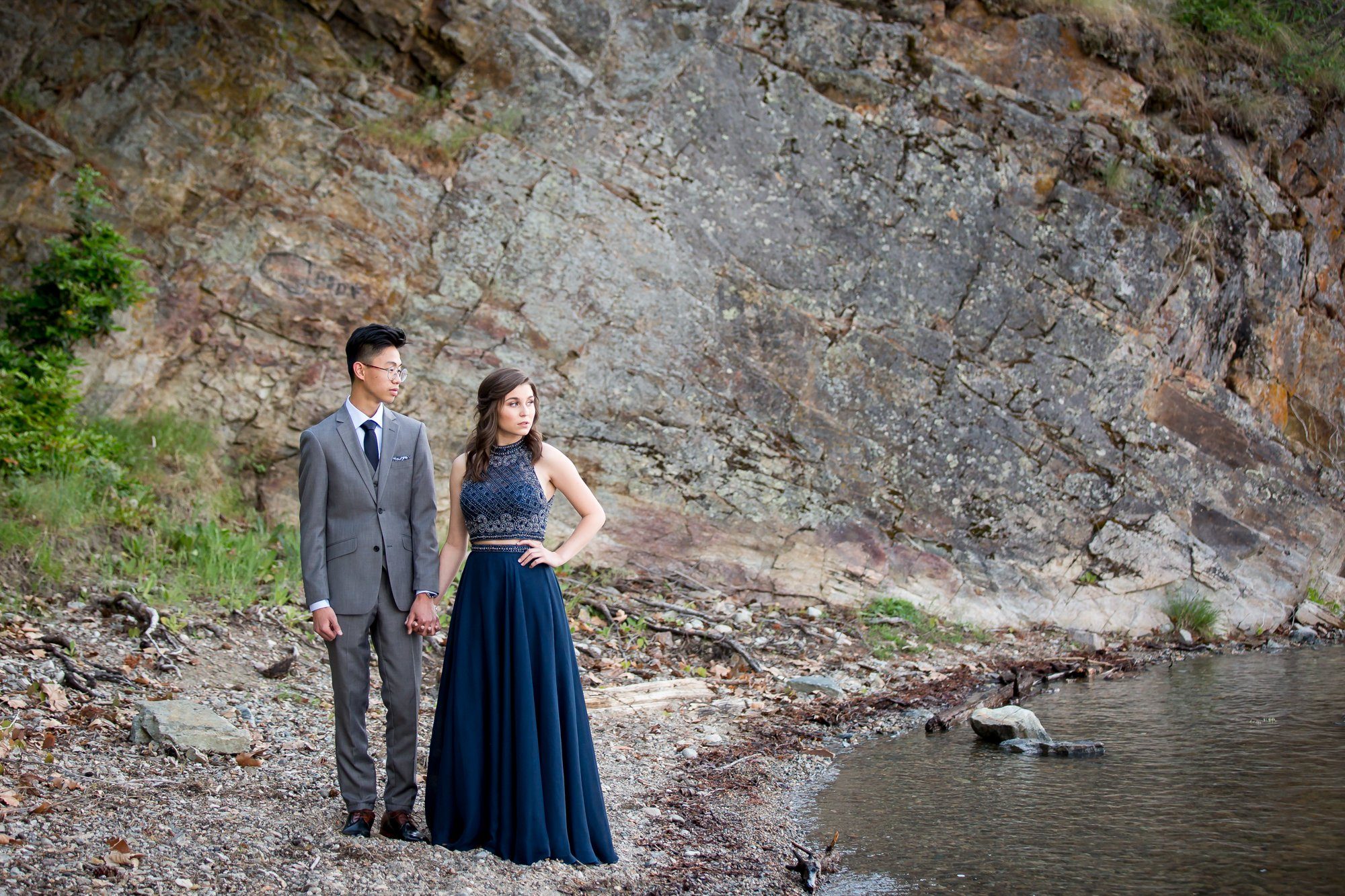 A graduating couple standing on the shore