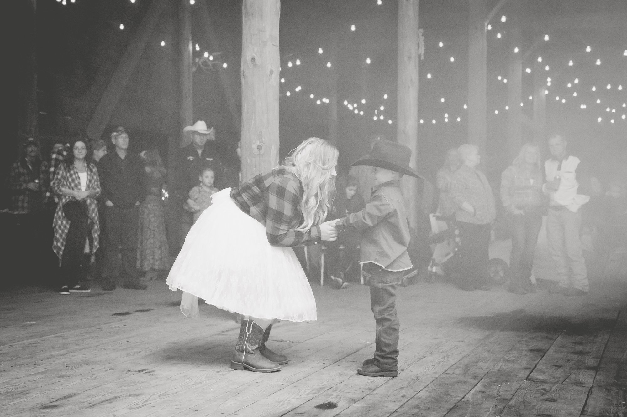 A bride dancing with her son in a barn